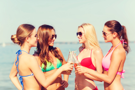 bachelorette party: summer vacation, holidays, travel and people concept - group of smiling young women sunbathing and drinking on beach
