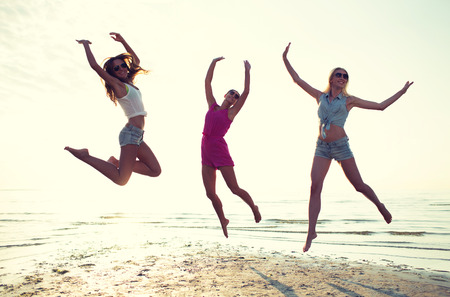 friendship, summer vacation, freedom, happiness and people concept - group of happy female friends dancing and jumping on beach Stock Photo