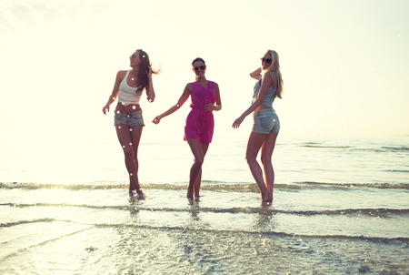 friendship, summer vacation, party, happiness and people concept - group of happy female friends dancing on beach photo