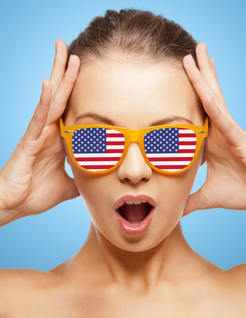 julio: la gente, patriotismo, orgullo nacional y el concepto de día de la independencia - adolescente feliz en cortinas con bandera americana Foto de archivo