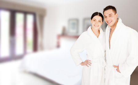 travel background: people, travel, tourism, vacation and honeymoon concept - happy couple in bathrobes over spa hotel room background