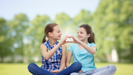 cute girlfriends: people, children, friends and friendship concept - happy little girls sitting and showing heart shape hand sign over summer park background