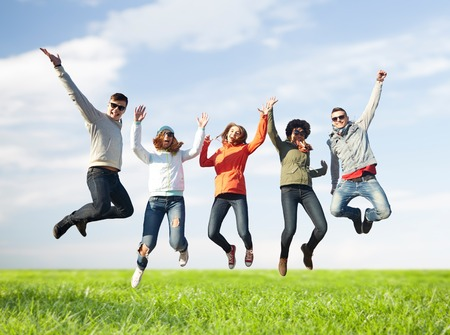 sky and grass: people, freedom, happiness and teenage concept - group of happy friends in sunglasses jumping high over blue sky and grass background Stock Photo