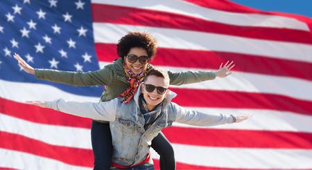 familia unida: amistad internacional, la libertad y el concepto de la gente - pareja adolescente feliz en tonos que se divierten sobre fondo de bandera Foto de archivo