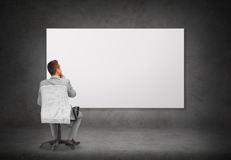 empty office: business, people and advertisement concept - businessman in suit sitting in office chair over blank white board or screen on gray wall background from back