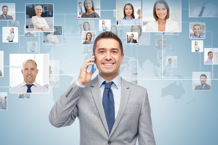 future business: global business, people, network, communications and technology concept - happy businessman calling on smartphone over blue background with world map and contacts icons
