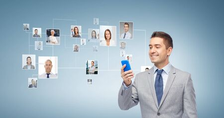 network people: business, people and technology concept - happy businessman texting or reading message on smartphone over blue world map and network contacts background
