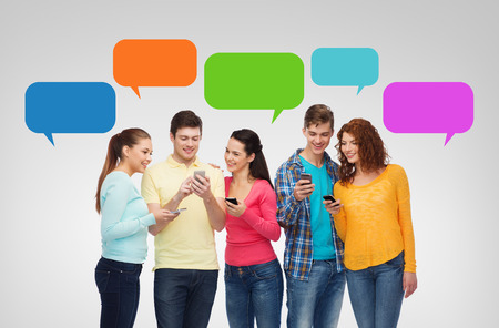 Messenger: friendship, technology, communication and people concept - group of smiling teenagers with smartphones over messenger text bubbles and gray background Stock Photo