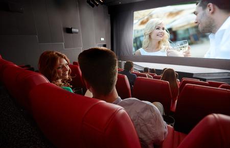 teatro: el cine, el entretenimiento, la comunicación y el concepto de la gente - feliz pareja de amigos viendo películas y hablando en el teatro de la parte posterior