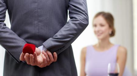 pareja, el amor, la propuesta y el concepto de vacaciones - cerca de hombre que se esconde detrás de la caja roja de la mujer en el restaurante