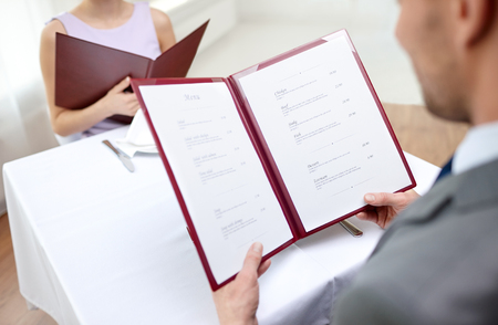 food menu: restaurant, food, eating and holiday concept - close up of couple with menu choosing dishes at restaurant Stock Photo