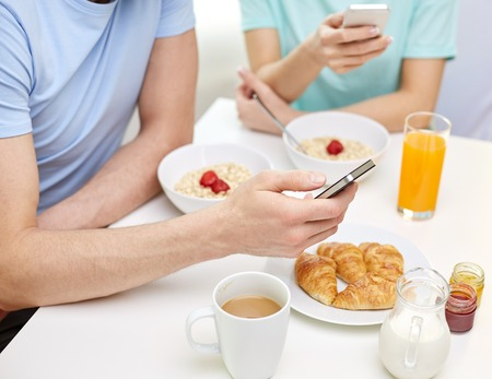 healthy eating: food, eating, people and healthy food concept - close up of couple having breakfast and texting on smartphones at home