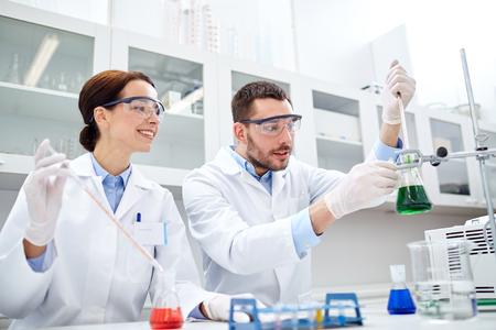 la science, la chimie, la biologie, la pharmacie et les gens le concept - les jeunes scientifiques à la pipette et fiole décision test ou de la recherche en laboratoire clinique