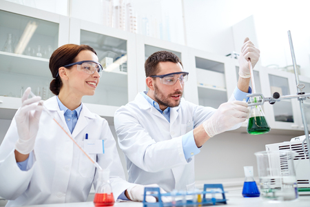 exam results: science, chemistry, biology, pharmacy and people concept - young scientists with pipette and flask making test or research in clinical laboratory