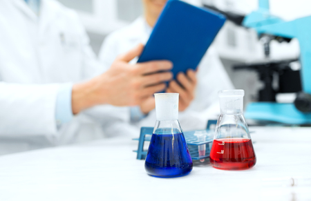 tablet computer: science, chemistry, technology, biology and people concept - close up of scientists with glass tes flasks and tablet pc computer on table in lab