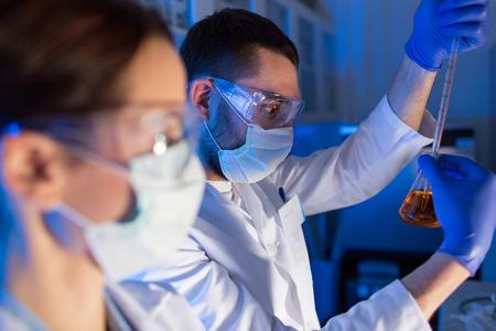 la ciencia, la química, la biología, la medicina y el concepto de la gente - cerca de los jóvenes científicos con pipetas y frascos que hacen prueba o investigación en laboratorio clínico