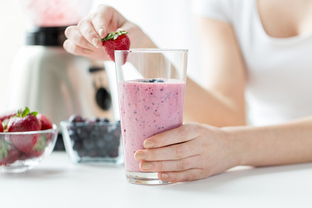 nutrition: healthy eating, cooking, vegetarian food, dieting and people concept - close up of woman hands decorating milkshake with strawberry at home Stock Photo
