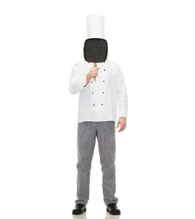 covering face: cooking, profession and people concept - male chef cook covering face or hiding behind grill pan Stock Photo