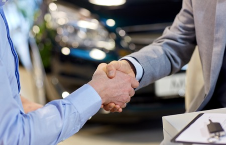 auto business, car sale, deal, gesture and people concept - close up of male handshake in auto show or salon Stock Photo