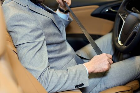 men in suit: safety, driving and people concept - close up of man in elegant business suit fastening seat safety belt in car