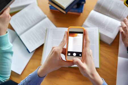 mobile app: people, education, technology and exam concept - close up of students with smartphones taking picture of books page and making cheat sheet in school library Stock Photo