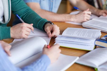education: 사람들, 학습, 교육 및 학교 개념 - 가까운 책이나 교과서 노트북에 쓰는 학생들의 손을 닫