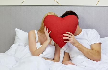 ロマンス: 旅行、愛、バレンタインの日、休日と幸福コンセプト - ホテルや家庭で赤いハート形の枕の後ろに顔を隠してベッドで幸せなカップル