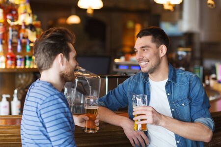 pubs: people, men, leisure, friendship and communication concept - happy male friends drinking beer and talking at bar or pub