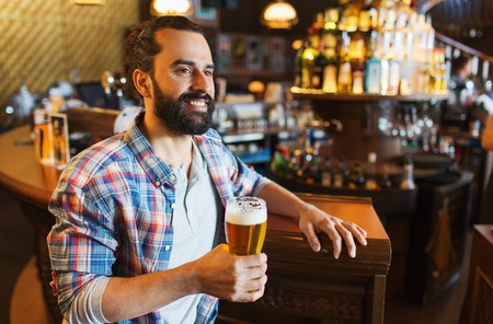 alcohol drinks: people, drinks, alcohol and leisure concept - happy young man drinking beer at bar or pub Stock Photo