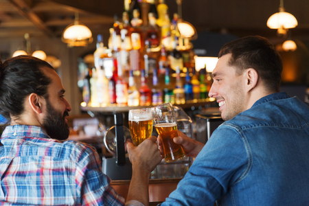 best party: people, leisure, friendship, communication and bachelor party concept - happy male friends drinking beer and talking at bar or pub from back Stock Photo
