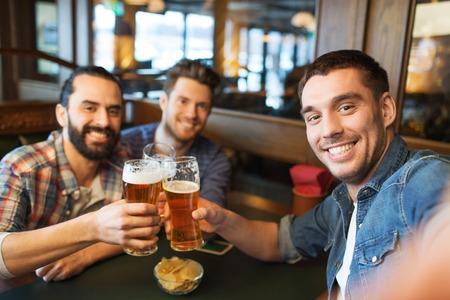 la gente, el ocio, la amistad, la tecnología y el concepto de la despedida de soltero - amigos varones feliz que toma la autofoto y bebiendo cerveza en el bar o pub