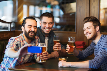 guys: people, leisure, friendship, technology and bachelor party concept - happy male friends with smartphone taking selfie and drinking beer at bar or pub Stock Photo