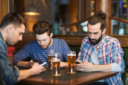 pub: people, men, leisure, friendship and technology concept - male friends with smartphones drinking beer at bar or pub