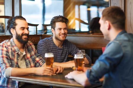 jovenes tomando alcohol: gente, hombres, ocio, la amistad y el concepto de comunicación - amigos hombres felices bebiendo cerveza en el bar o pub