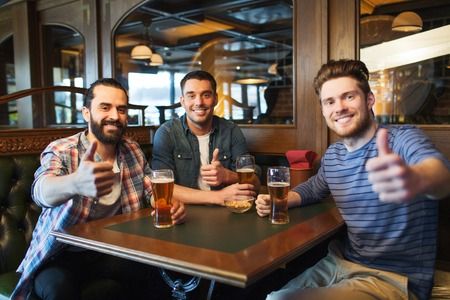 pubs: people, leisure, friendship and and bachelor party concept - happy male friends drinking beer and showing thumbs up at bar or pub