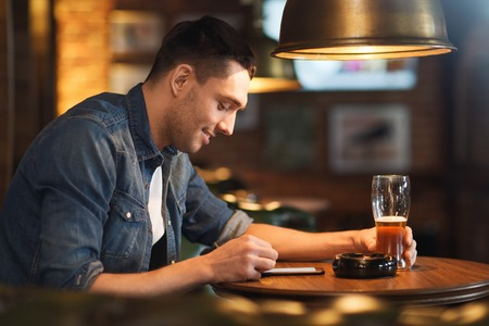 smartphone addiction: people and technology concept - happy man with smartphone drinking beer and reading message at bar or pub Stock Photo