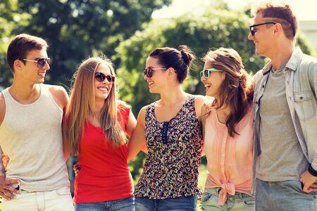 pareja de adolescentes: amistad, ocio, verano y concepto de la gente - grupo de amigos que sonríen al aire libre