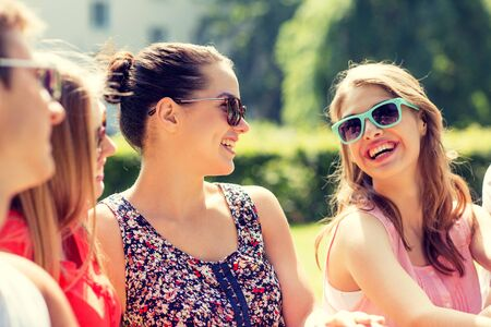 laugh: friendship, leisure, summer and people concept - group of smiling friends outdoors sitting on grass in park