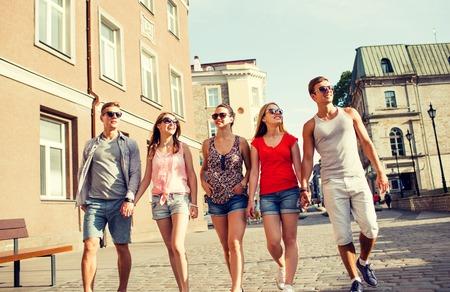 personas en la calle: amistad, ocio, verano, gesturer y la gente concepto - grupo de amigos sonrientes caminando y tomados de la mano en la ciudad