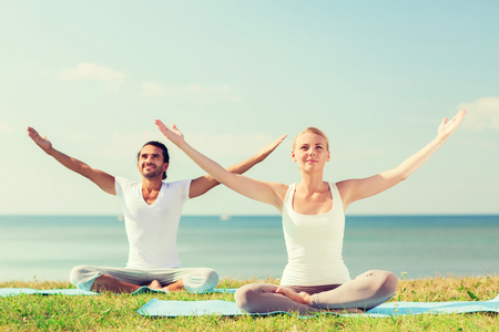 sport fitness: fitness, sport, friendship and lifestyle concept - smiling couple making yoga exercises sitting on mats outdoors