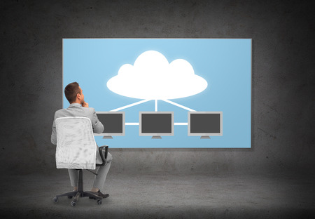 server technology: business, people, transferring data and technology concept - businessman in suit sitting in office chair over screen with cloud and server computers on gray wall background from back