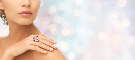 mooie vrouwen: Schoonheid, sieraden, mensen en accessoires concept - close-up van vrouw met cocktail ring aan de hand over blauwe vakantie lichten achtergrond