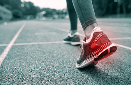 sports track: fitness, sport, sports injury, pain and people concept - monochrome close up of woman feet or legs running on track with red spot from back