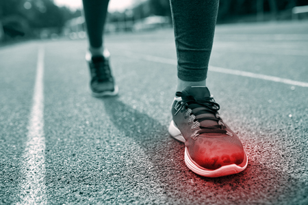 sports track: fitness, sport, sports injury, pain and people concept - monochrome close up of woman feet or legs running on track with red spot Stock Photo