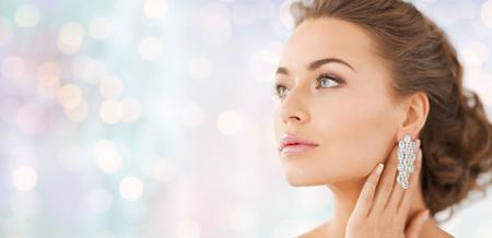 mensen, schoonheid, sieraden en accessoires concept - mooie vrouw met diamanten oorbellen over blauwe vakantie achtergrond verlichting Stockfoto