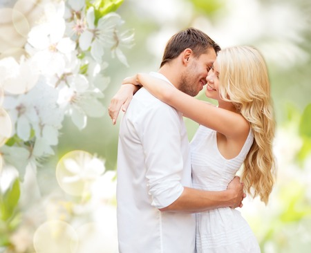 people, romance, love and dating concept - happy couple hugging over green blooming summer garden background