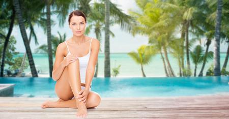 piernas mujer: gente, belleza, spa, viajes y el concepto de resort - hermosa mujer en ropa interior de algodón tocando sus piernas por encima de la piscina en la playa con palmeras de fondo