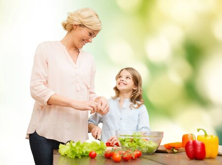 vegetarian food, culinary, family and people concept - happy mother and daughter cooking vegetable salad for dinner and talking over summer house background