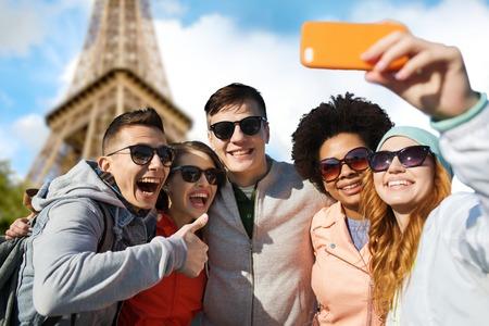 famille africaine: gens, Voyage, tourisme, l'amitié et de la technologie concept - groupe heureux amis adolescents prenant selfie avec smartphone et montrant thumbs up sur paris tour eiffel fond