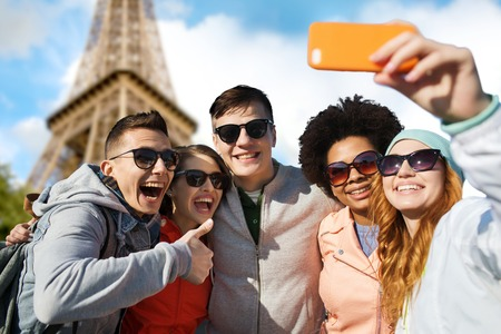 multiracial family: people, travel, tourism, friendship and technology concept - group of happy teenage friends taking selfie with smartphone and showing thumbs up over paris eiffel tower background Stock Photo